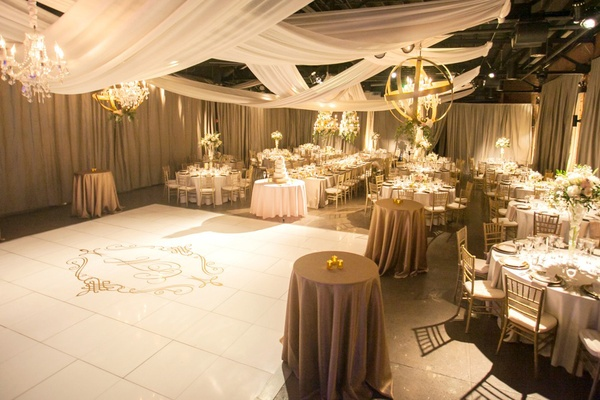 a white reception space dance floor with the couples initials in calligraphy