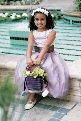 Flower girl wearing light purple dress with a dark purple sash holding a basket of flowers