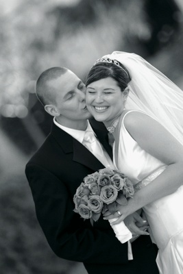 Black and white image of groom kissing bride's cheek
