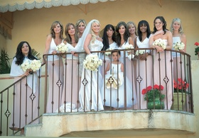 Bride and bridesmaids wearing white blouses and long pink skirts