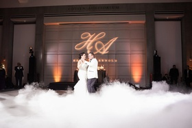 bride in martina liana trumpet gown dances with groom in white tuxedo jacket fog first dance