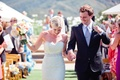 Bride and groom holding hands exit wedding