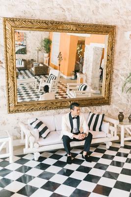 wedding portrait groom in colombia on white sofa black white checker floor gold mirror lobby hotel
