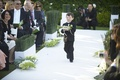 Ring bearer walking down white aisle lined with bamboo