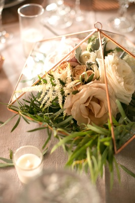 Wedding reception candle votive next to rose gold copper terrarium with rose flowers greenery