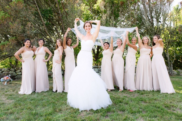 Bridesmaids in mismatched long bridesmaid dresses holding veil bride in Pnina Tornai for Kleinfeld