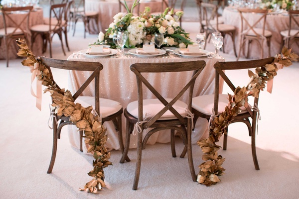 DeMarco Murray and wife three person sweetheart table for their daughter gold garland on back chairs