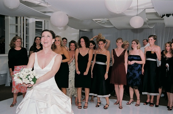 Bride prepares to toss bouquet to bridesmaids and guests