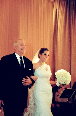 Father walking bride down aisle arm in arm