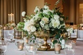 Ivory peony and rose flowers with greenery in gold footed vase white tablecloth candle votives