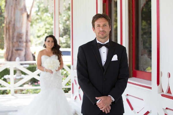 Groom in tuxedo and bow tie white pocket square waiting patiently for bride during first look