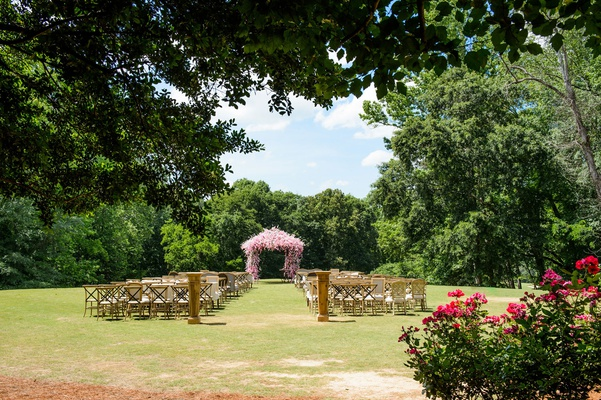 Wedding ceremony on grass lawn pink chuppah white flowers vineyard chairs wood and grass aisle