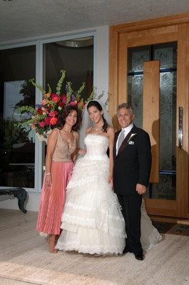 Bride with mother and father in front of flower arrangements
