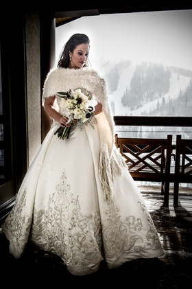 Bride wearing furry shawl and embroidered gown