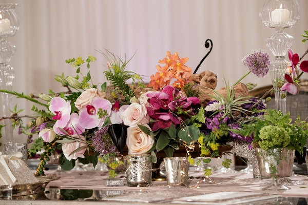 pink orchids, ivory roses, orange flowers, greenery, votives in mercury glasses