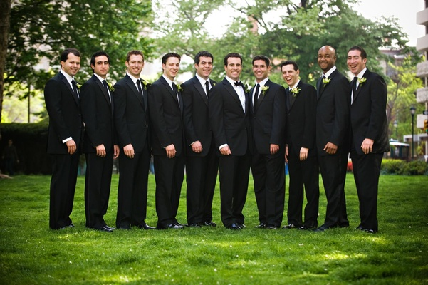 Groom in tuxedo and bow tie and groomsmen in tuxedos and ties