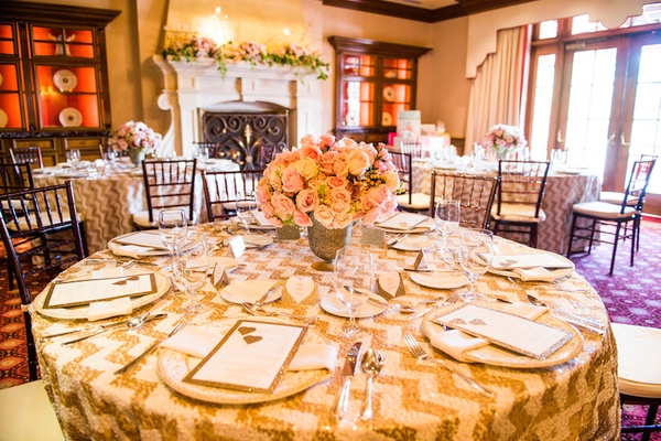wedding shower table with a floral arrangement of pink white roses in golden vase
