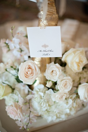 White square seating card with gold motif