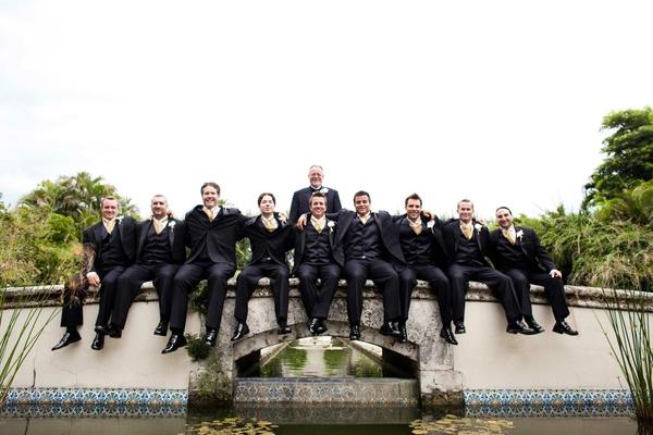 Groom and groomsmen sitting on Mediterranean bridge