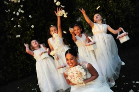 Four flower girls throw white rose petals on top of bride