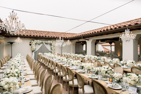 outdoor wedding reception bacara long wood tables with low centerpieces crystal chandelier overhead