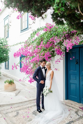 bride in francesca miranda wedding dress, butterfly appliques, plunging neckline, groom navy tux