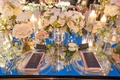 Mirror wedding reception table with clusters of white flowers and candlelight evening rooftop dinner