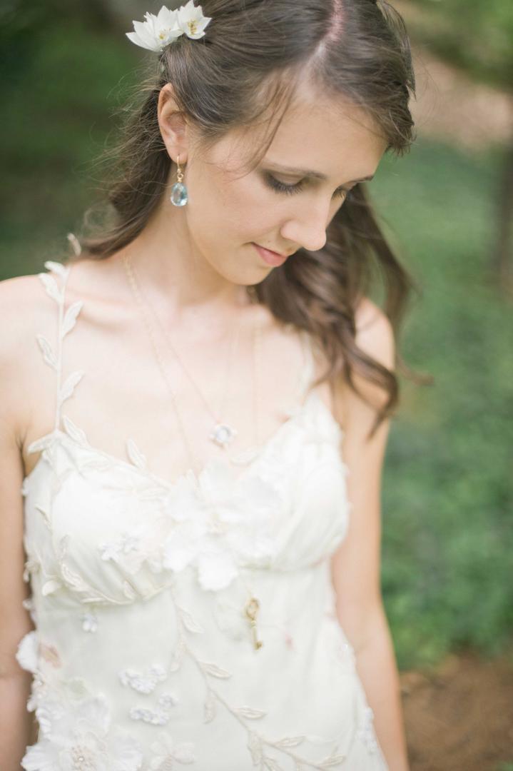 Bride wearing light blue earrings and key necklace