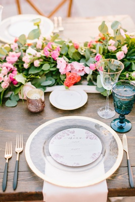 wood table gold black flatware gold charger plate blush napkin blue goblet pink orange flowers green