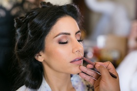 Bride getting makeup done on wedding day hair pulled back natural makeup pink lip and eyeshadow