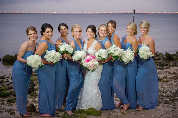 Bride with bridesmaids barefoot in the sand