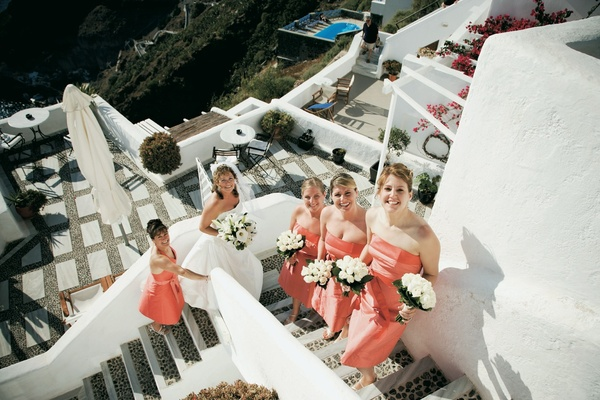 Coral bridesmaid gowns on stairs of Santorini