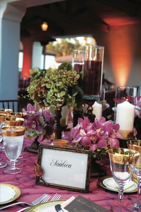 Purple tablecloths with orchid centerpiece and gold rimmed glasses