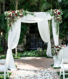 chuppah with greenery and red, blush, and ivory florals, rose petal aisle, waterfall