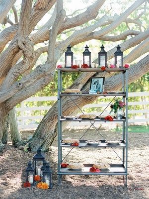 Outdoor wedding with shelving unit and pies decorated with Moroccan lanterns