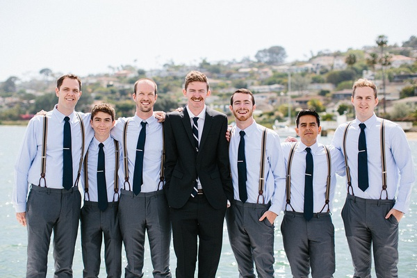 Groom and groomsmen in charcoal pants, light blue shirts, navy blue ties, tie clips, and suspenders