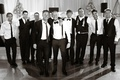 Black and white photo of groomsmen at reception