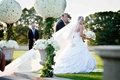 Bride in a strapless Pnina Tornai ball gown and veil with groom in a black tuxedo exit ceremony