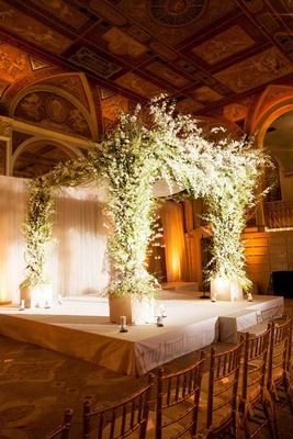 Chuppah decorated with white flowers and greenery