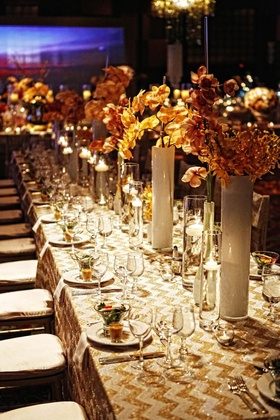 Wedding reception table with gold and white chevron design and orchid stems in milky vases