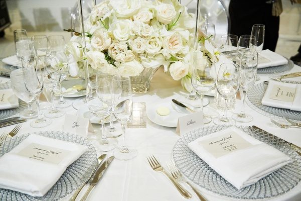 crystal chargers, gold flatware, cream centerpieces white rose flowers