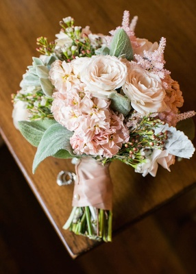 Bride's bouquet of pale pink roses, astilbes, greenery bound by pink ribbon