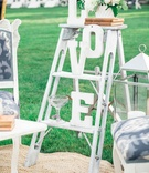 small white ladder with letters that spell out LOVE large lantern and white blue settees and rug
