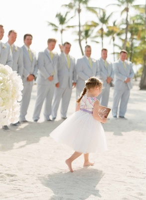 Flower girl in tulle skirt with colorful bodice carries sign at beach wedding ceremony