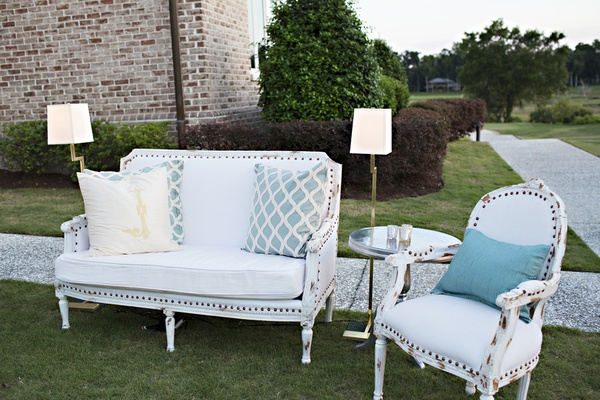 Outdoor lounge area with vintage white seating and blue and white throw pillows