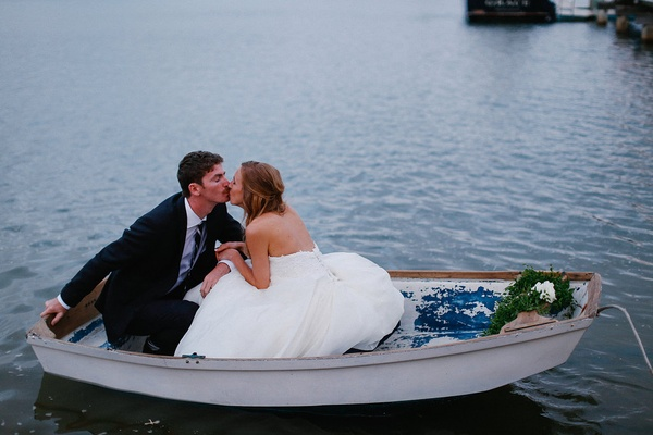 Groom in black suit kisses bride in a strapless Martina Liana dress as they sit in a white rowboat