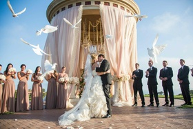 Bride and groom kiss among flying doves