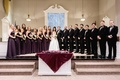 Baptist church wedding ceremony alter with bridesmaids in purple and groomsmen in suits bow ties