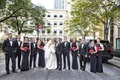 Bride and groom with groomsmen in tuxedos and bridesmaids in black dresses with peplum detail