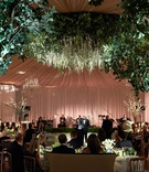 wedding reception flower chandelier tented ballroom drapery head table dance floor live band low